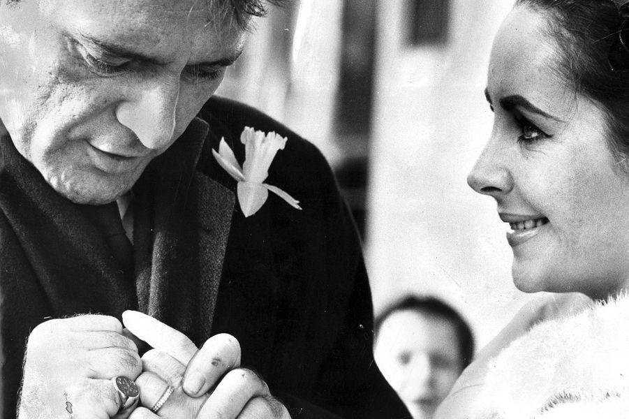 """Elizabeth Taylor et Richard Burton se rencontrent en 1963 sur le tournage du film """"Cléopâtre"""" dans lequel elle incarne le rôle principal, tandis que l'acteur joue son amant Antoine. Quelques mois après ça, Richard Burton divorce de sa première femme pour épouser Liz Taylor en mars 1964. Le couple adopte une petite fille mais divorce une première fois dix ans plus tard. Ils s'unissent une nouvelle fois à l'automne 1975 pour divorcer à nouveau moins d'un an après, leur passion s'essoufflant par les crises."""