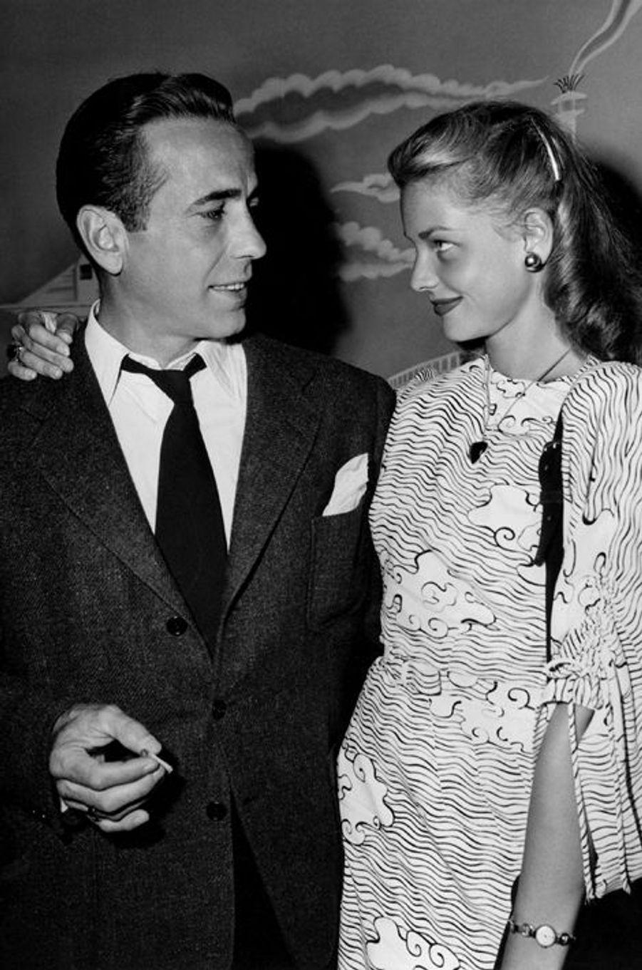 """Le réalisateur Howard Hawkes impose à Humphrey Bogart la très jeune Lauren Bacall comme partenaire pour son film """"Le Port de l'angoisse"""" en 1944, après l'avoir repérée en couverture de """"Harper's Bazaar"""". D'abord réfractaire à l'idée de donner la réplique à une inconnue de 19 ans, l'acteur tombe finalement sous son charme. Malgré leurs 26 ans d'écart, ils se marient au printemps 1945 et resteront ensemble jusqu'au décès de l'acteur, en 1957."""