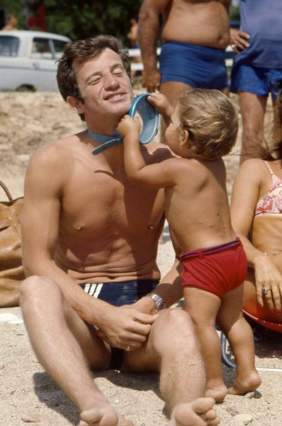 Été 1964, Jean Paul Belmondo en vacances en famille à Beauvallon près de Saint-Tropez. Des vacances bien méritées car l'année 1964 a été pour Jean-Paul un festival de grands rôles qui ont fait de lui une grande star adorée des Français, avec entre autre «L'Homme de Rio», «Week-end à Zuydcoote», et «Cent-mille dollars au soleil». On le voit ici entrain de jouer sur la plage avec son fils Paul.