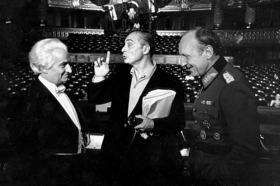 1966. Dans les coulisses du tournage de «La grande vadrouille», le film aux 17 millions de spectateurs. Il a été pendant 30 ans le plus grand succès cinématographique en France avant d'être dépassé par Titanic de James Cameron en 1998 et aussi par «Bienvenue chez les Ch'tis» de Dany Boon en 2008. Ici lors des scènes tournées à l'Opéra de Paris, le trio magique du cinéma populaire, Louis De Funès, Gérard Oury et Bourvil. Il détient aussi le record de passage à la tv, 16 fois sur la première chaîne et 11 fois sur la deuxième chaîne.