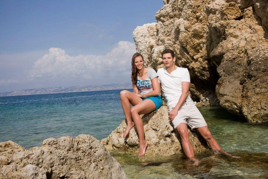 Les nageurs français Laure et Florent Manaudou posent sur des rochers, dans la crique qui jouxte le célèbre Club des nageurs de Marseille (CNM), auquel appartient le frère de la nageuse.