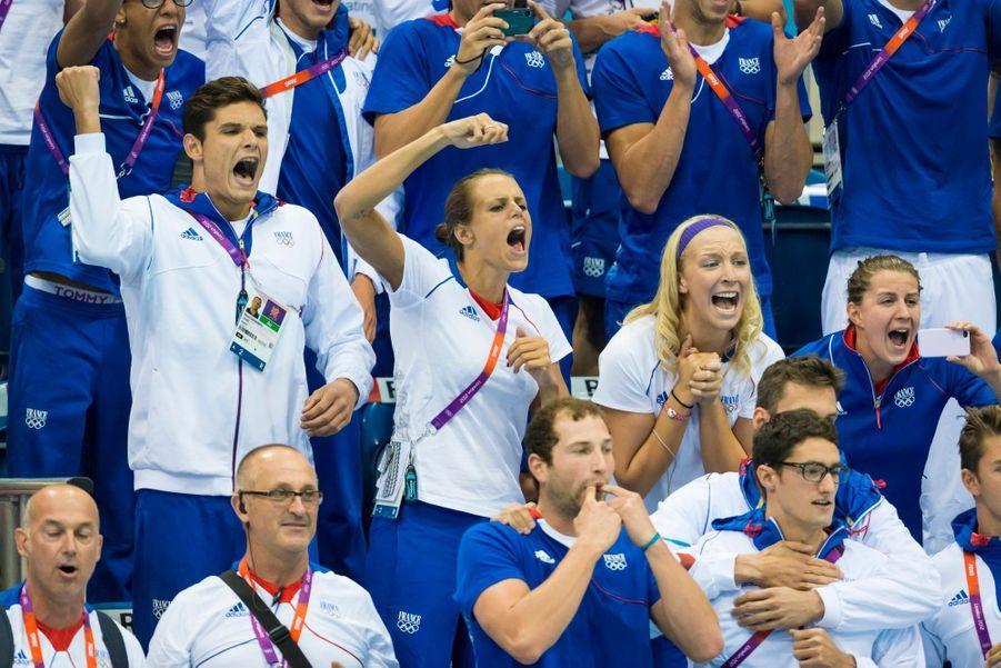 Laure et Florent Manaudou avec les membres de l'équipe de France encourageant les nageurs lors des Jeux Olympiques de Londres.