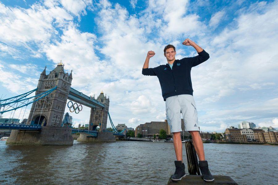 Florent Manaudou, 21 ans, médaillée d'or au 50 mètres nage libre, debout sur un ponton au bord de la Tamise, le Tower Bridge orné des anneaux olympiques en arrière-plan.