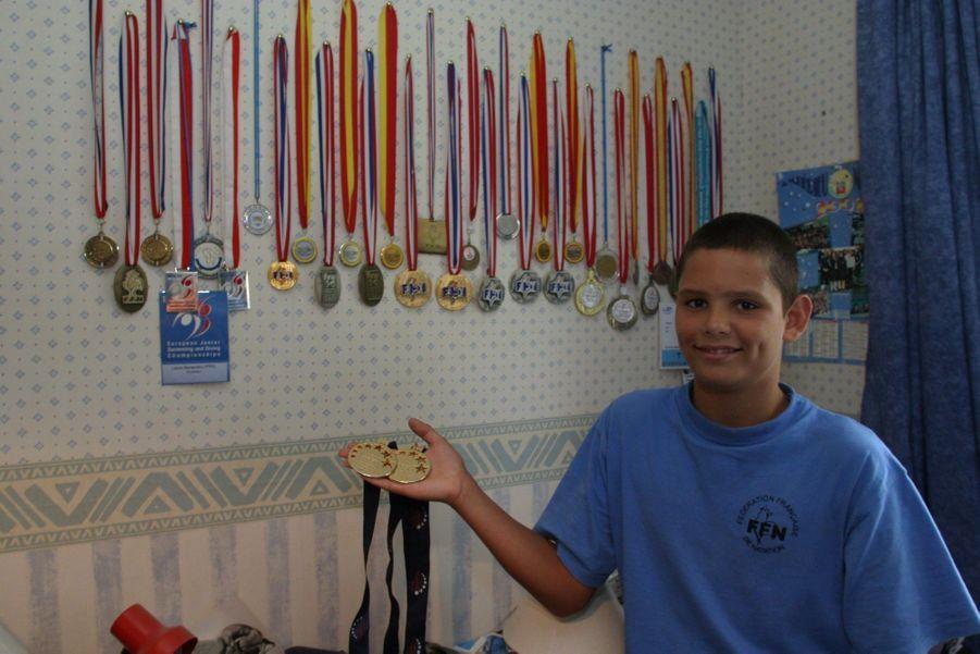 A 13 ans, montrant la collection de médailles trônant dans la chambre de sa soeur Laure, médaille d''or du 400 m nage libre aux Jeux olympiques d'Athènes en 2004.