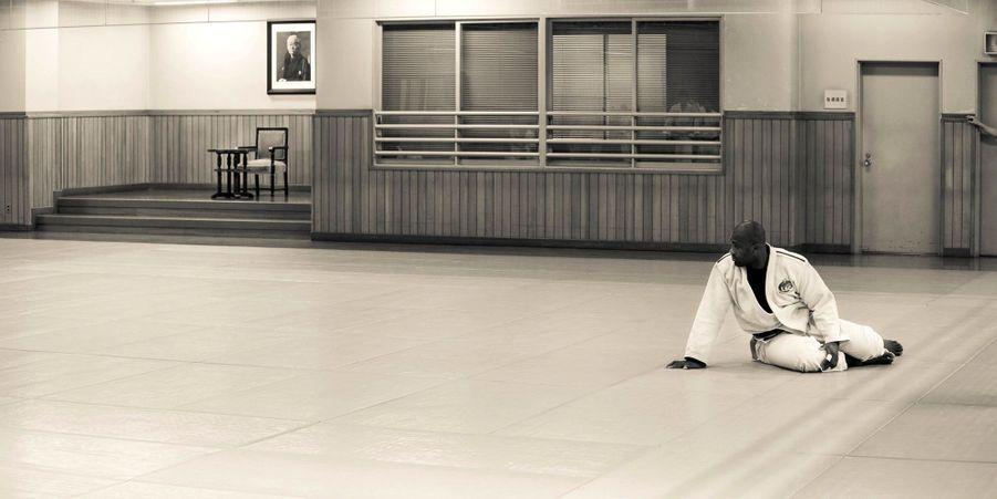 Sur un tatami, au Japon. A l'arrière plan, le portrait du créateur du judo, Jigoro Kano.