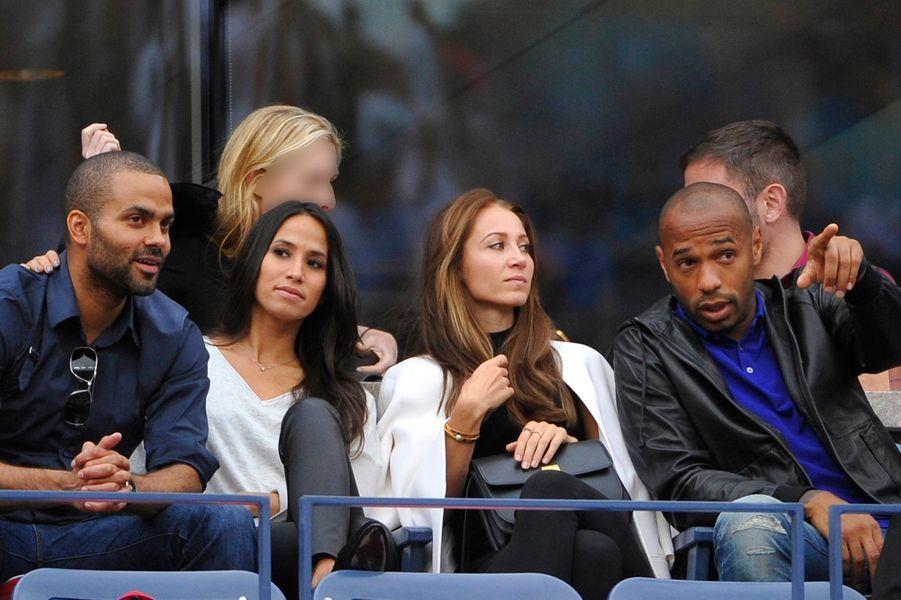 Tony Parker et son épouse Axelle Francine, et Thierry Henry et sa compagne Andrea Rajacic , à la finale de l'US Open à New York, le 8 septembre...