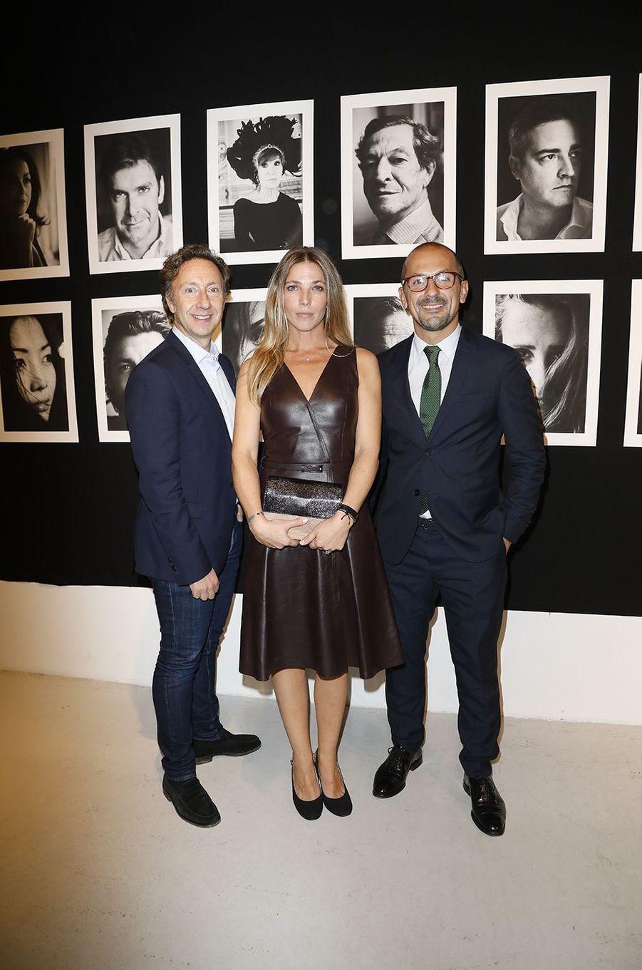 """Stéphane Bern et Lionel posent avec la photographe Alice Ralli au vernissage de l'exposition """"Trois cartes blanches"""", à Paris, le 10 octobre 2017."""