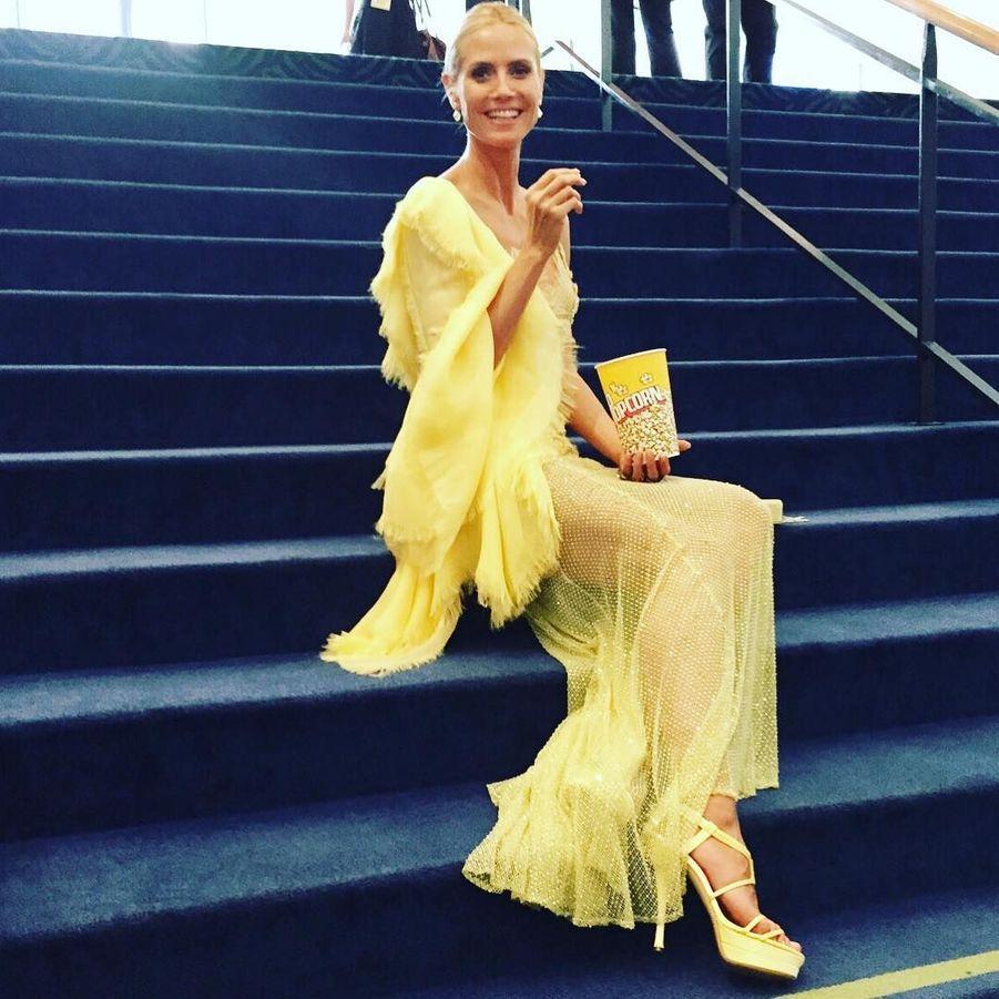Le mannequin Heidi Klum mange du popcorn assorti à sa robe Versace vaporeuse.