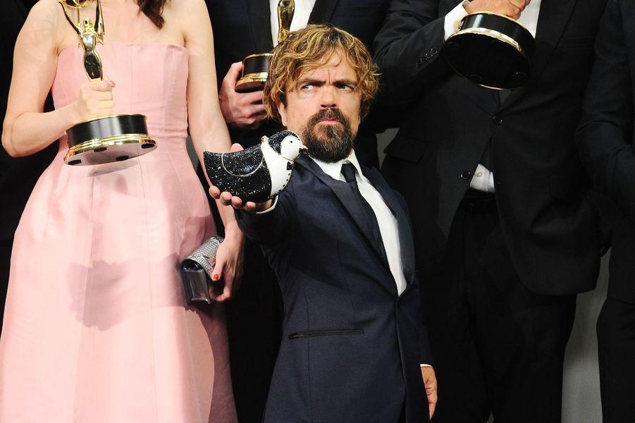 Tel un gentleman, l'acteur Peter Dinklage tient le sac à main en forme d'oiseau d'une de ses collègues le temps d'une séance photo.