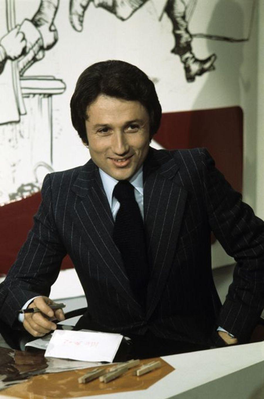 """En novembre 1975. L'animateur préféré des Français, tout sourire et stylo en main, assis dans le décor de l'émission """"Le Petit Rapporteur"""""""