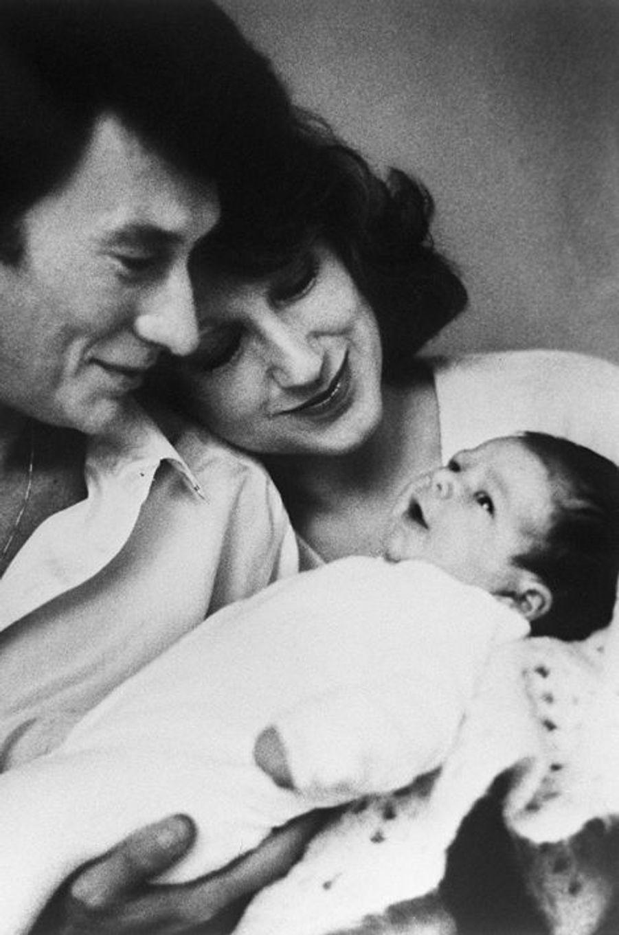 Le chanteur Johnny Hallyday et la comédienne Nathalie Baye contemplent leur petite fille, Laura, née le 15 novembre 1983 à l'hôpital américain...