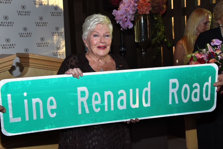 Line Renaud avec la pancarte de sa rue. L'objet prendra place au dessus de la porte de son bureau.