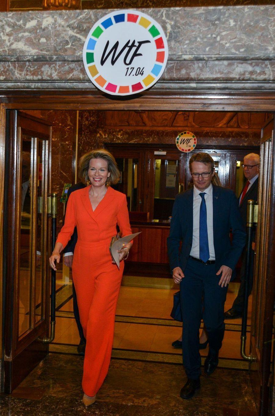 La reine Mathilde de Belgique en combinaison pantalon orange à Louvain, le 17 avril 2018