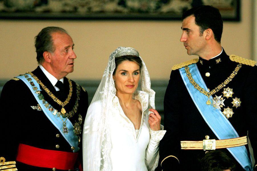 Le roi Juan Carlos Ier d'Espagne avec son fils le prince Felipe et son épouse Letizia Ortiz, le jour de leur mariage, le 22 mai 2004