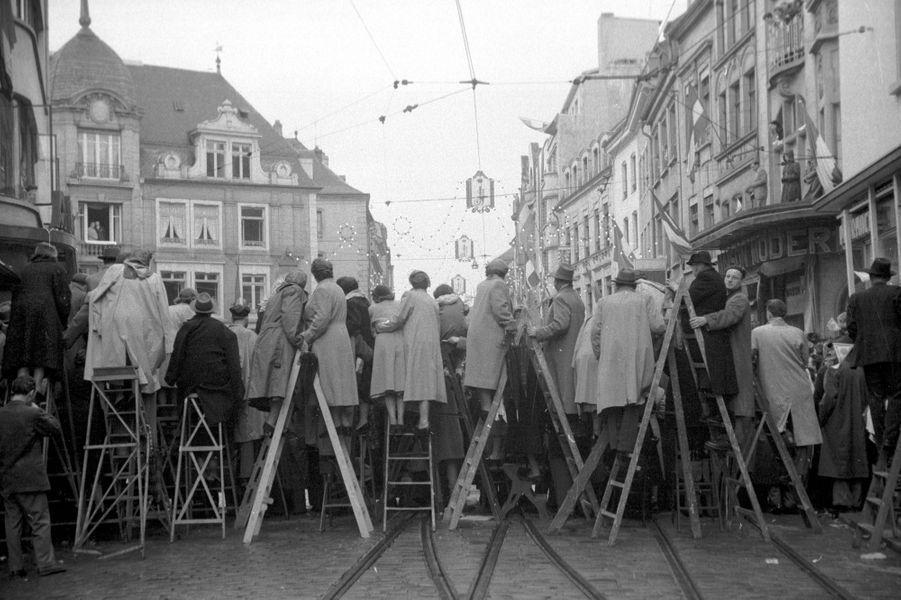Des spectateurs perchés sur des escabeaux le jour du mariage du grand-duc héritier Jean de Luxembourg et de la princesse Joséphine-Charlotte de Belgique, le 9 avril 1953