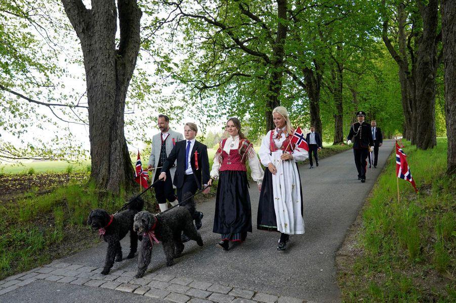 La princesse Mette-Marit et le prince Haakon de Norvège avec leurs enfants, la princesse Ingrid Alexandra et le prince Sverre Magnus et leurs chiens à Asker, le 17 mai 2020