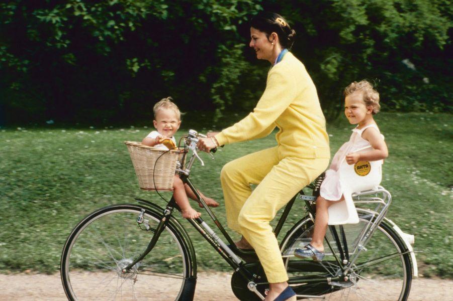 Le prince Carl Philip de Suède avec sa grande soeur la princesse Victoria et leur mère la reine Silvia, dans l'été 1980