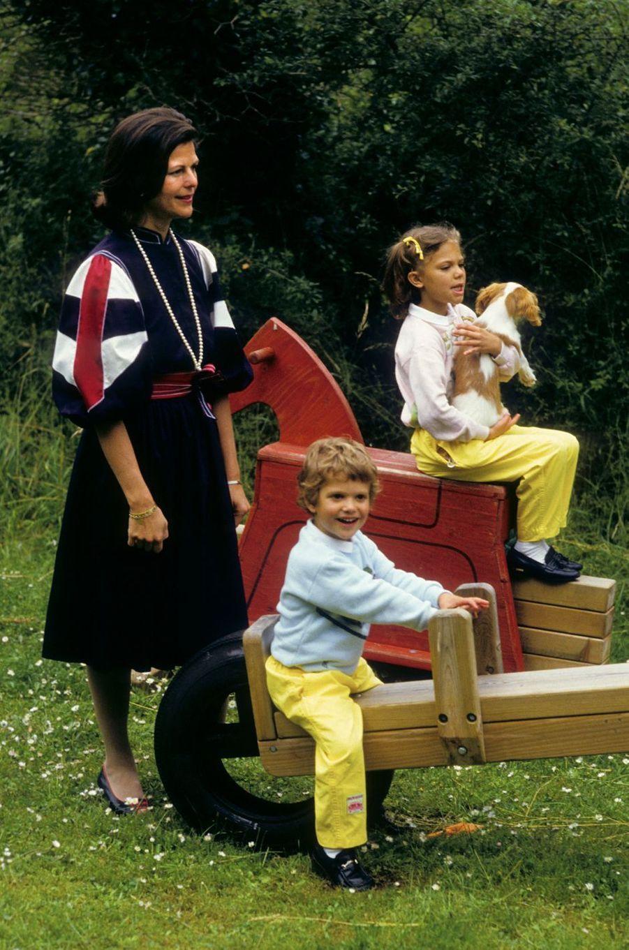 Le prince Carl Philip de Suède avec sa grande soeur la princesse Victoria et leur mère la reine Silvia, en 1984