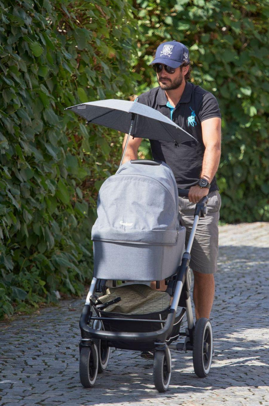Le prince Carl Philip de Suède promène son bébé le prince Alexander à Bastad, le 4 août 2016