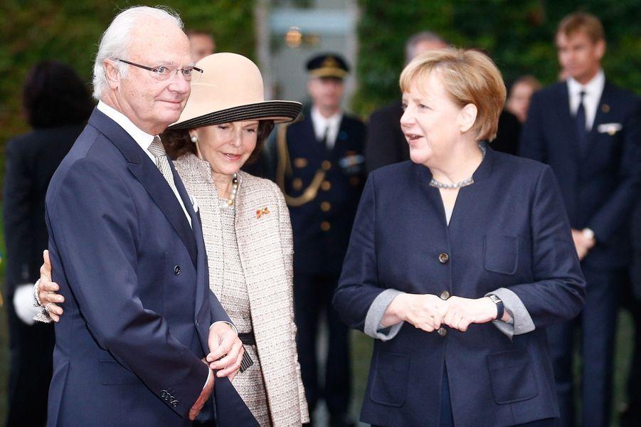 La reine Silvia et le roi Carl XVI Gustaf de Suède avec la chancelière allemande Angela Merkel à Berlin, le 5 octobre 2016