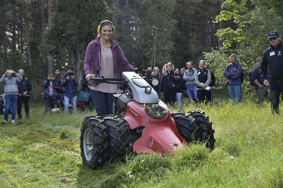 La princesse Victoria de Suède conduit une motofaucheuse dans l'Uppland, le 12 septembre 2018
