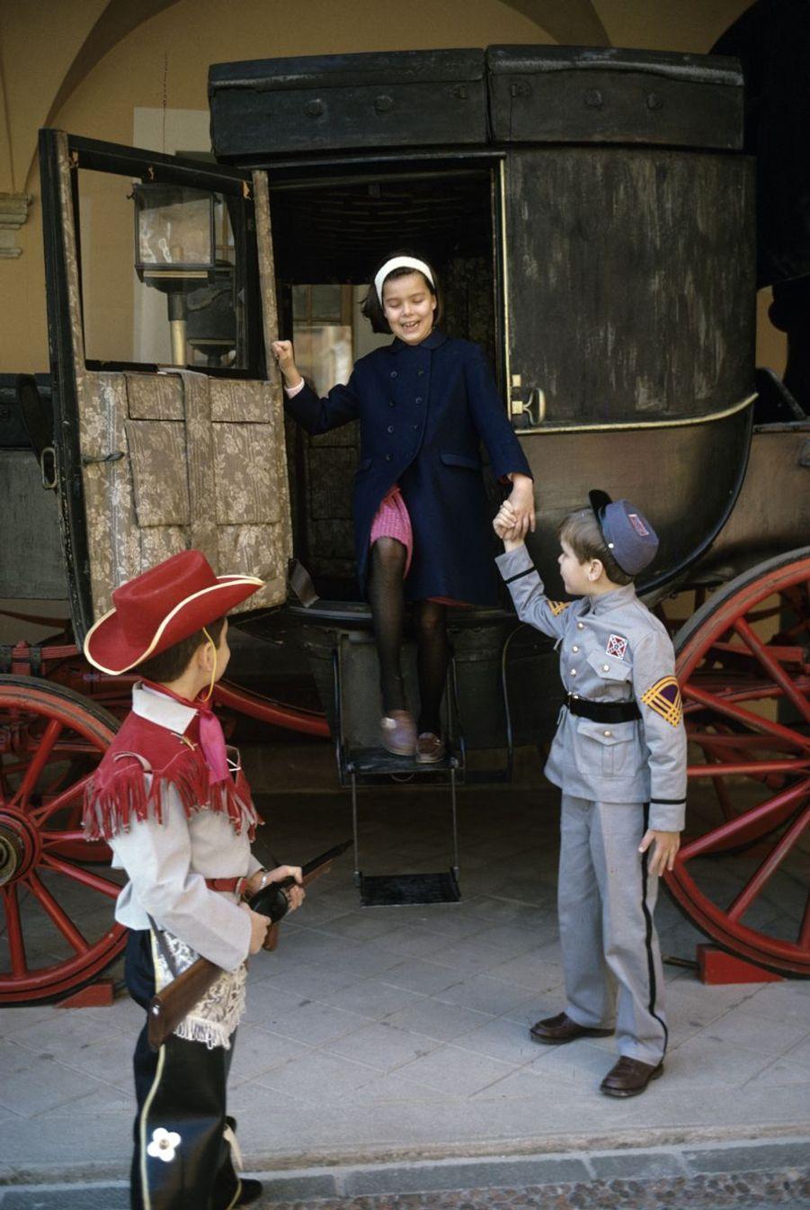Le prince Albert, 8 ans, joue aux cowboys avec son camarade Fabrice Notari et sa sœur la princesse Caroline, dans les jardins du palais.