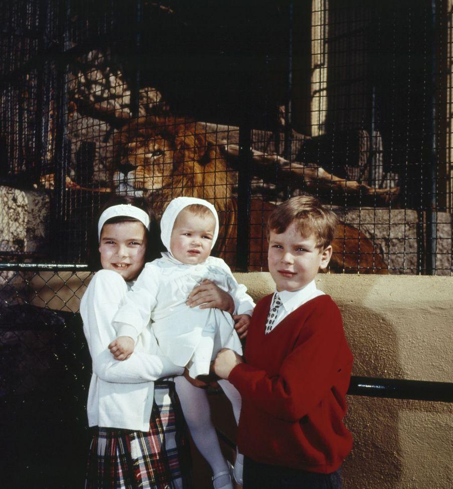 Le prince Albert avec ses soeurs les princesses Caroline et Stéphanie posent devant la cage des lions, dans le zoo du palais.