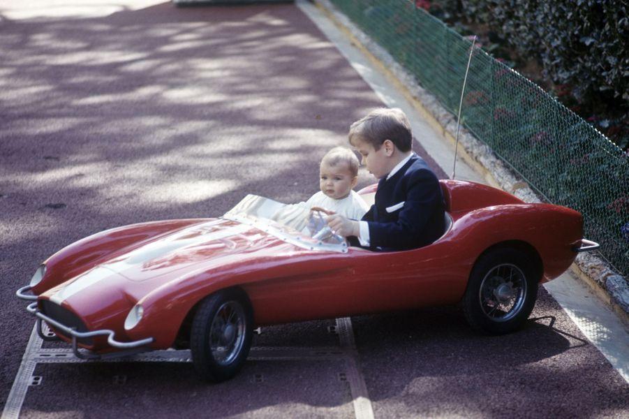 Le prince Albert conduit sa petite sœur Stéphanie dans une voiture d'enfant, dans les jardins du palais.