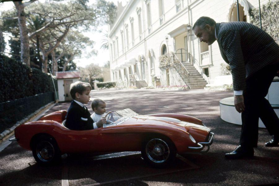 Le prince Albert conduit sa petite sœur Stéphanie dans une voiture d'enfant, sous le regard de leur père Rainier, dans les jardins du palais.