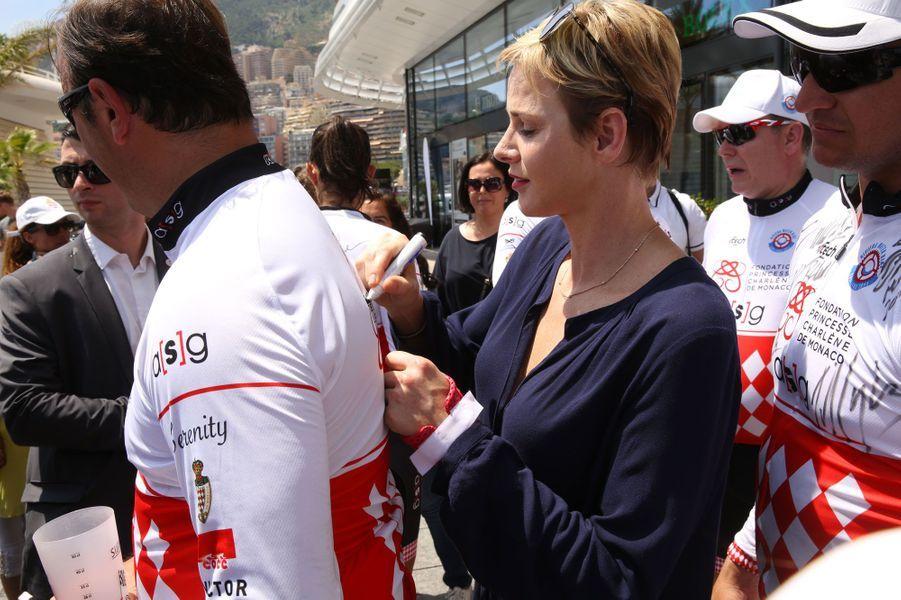 La princesseCharlène dédicace le maillot d'un concurrent.