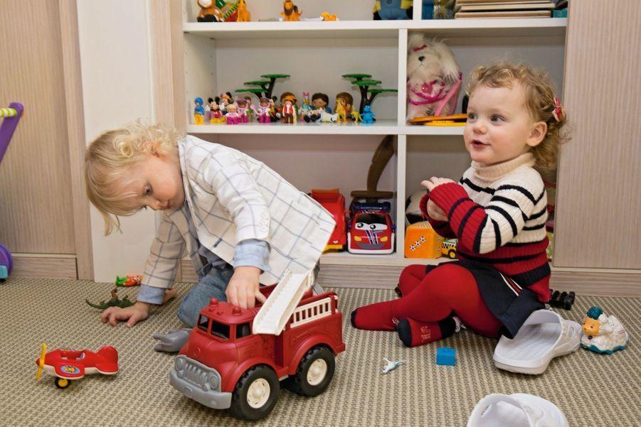 Jacques, concentré, joue avec un camion. Plus dissipée, Gabriella babille.