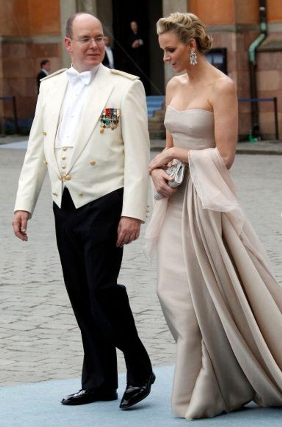 Pour le mariage princier, elle s'était drapée dans une robe bustier en crêpe de soie crème, agrémentée d'une étole rose pâle. Les cristaux de la minaudière et des bijoux, en harmonie avec le chignon cranté, conféraient du glamour à cette tenue simple.