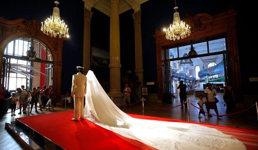 """Une semaine après la cérémonie religieuse et le mariage d'Albert II de Monaco et de Charlène Wittstock, une exposition consacrée à ce grand jour a été installée dans le cadre prestigieux de l'institut du centra océanographique de Monaco. Présentée par Stéphane Bern, """"L'histoire du Mariage Princier"""" sera visible jusqu'à la fin novembre. Elle a été conçue comme un parcours autour d'objets particulièrement symboliques du mariage, explique le site officiel. Le public pourra notamment découvrir les tenues du mariage, dont la magnifique robe Armani portée par Charlène."""