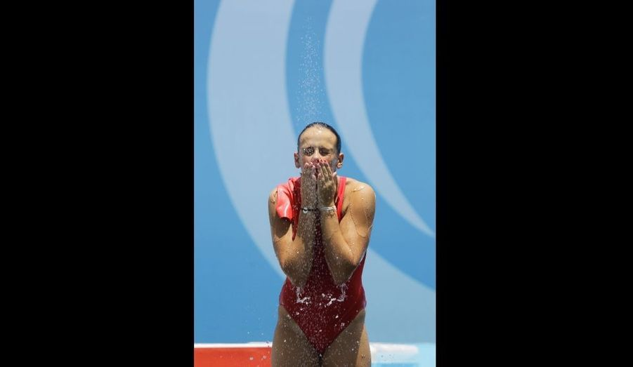 La plongeuse de 16 ans file rincer son maillot de bain rouge sous la douche après avoir quitté le bassin.