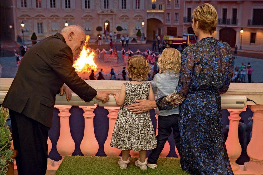 Vendredi 23 juin, sur le balcon du premier étage du palais, avec la princesse Charlène et le père Penzo, attendri par les jumeaux.
