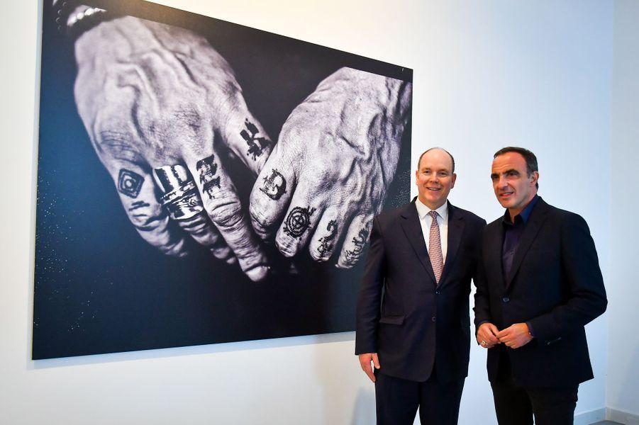 Le prince Albert II de Monaco et Nikos Aliagas devant la photo des mains de JoeyStarr à Monaco, le 5 avril 2018
