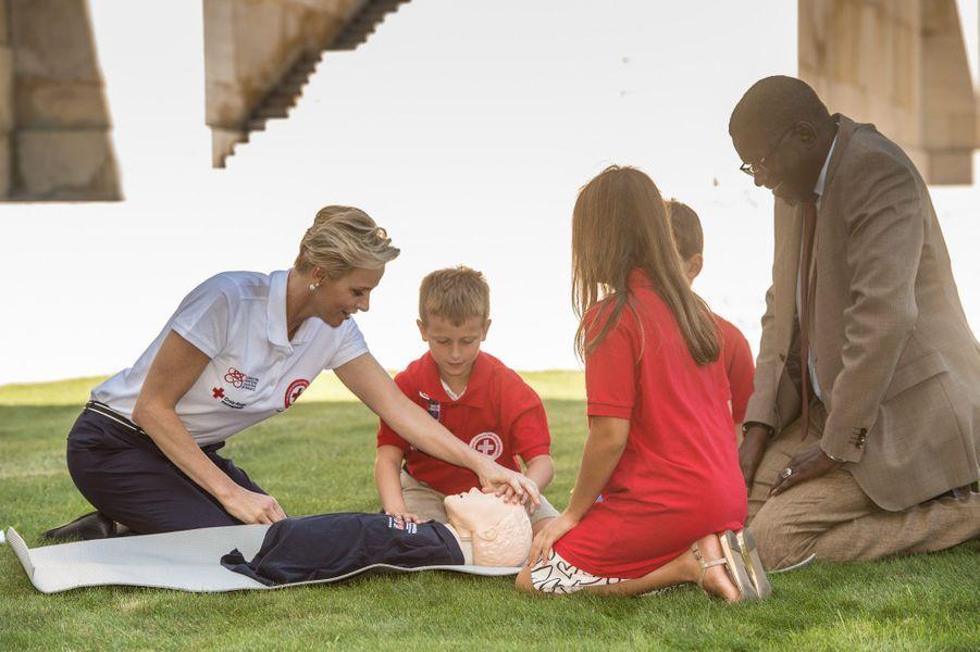 La princesse Charlène aux côtés d'enfants et du patron de la Croix-Rouge, Elhadj As Sy