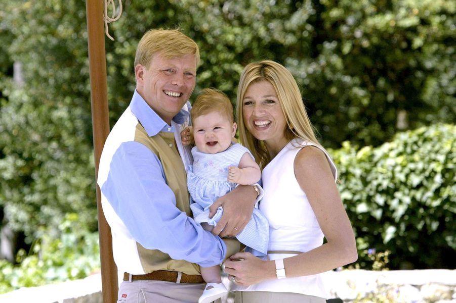 La princesse Catharina-Amalia dans les bras de son père et de sa mère en juillet 2004