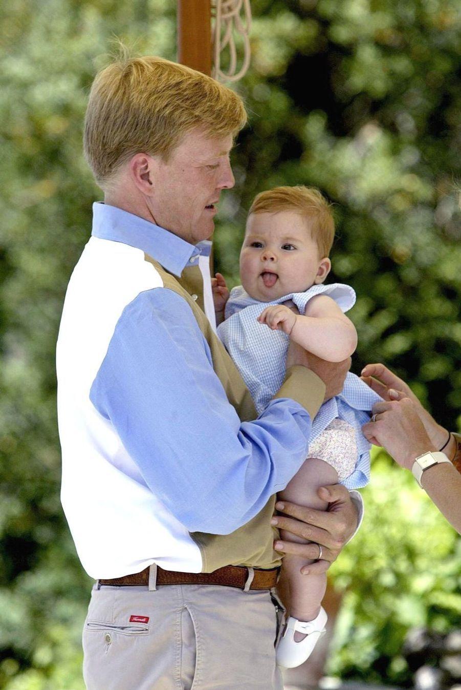 La princesse Catharina-Amalia dans les bras de son père Willem-Alexander en juillet 2004