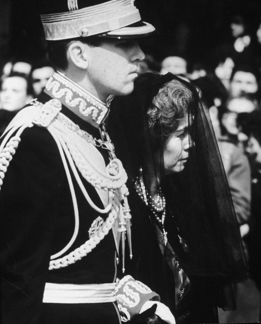 Le roi des Hellènes Constantin II avec sa mère la reine Frederika, lors des obsèques de son père le roi Paul Ier, en 1964