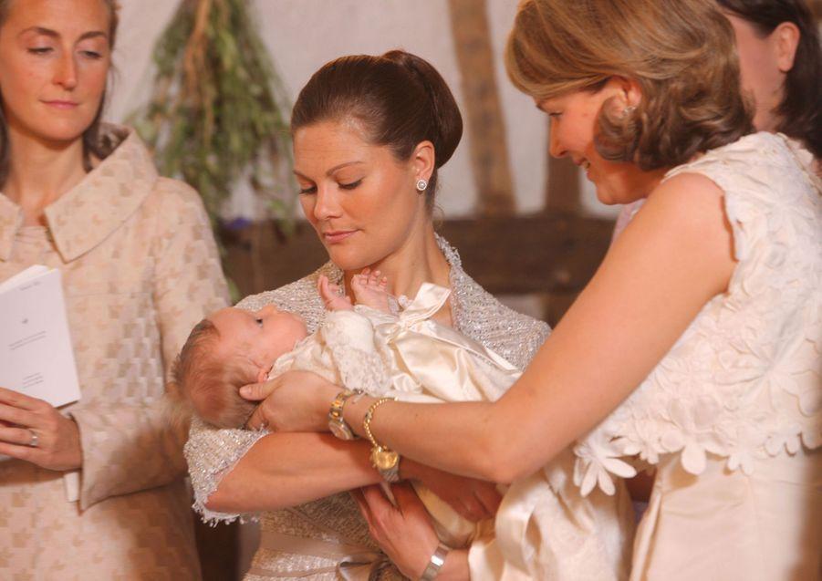 La princesse Eléonore de Belgique, le 14 juin 2008, jour de son baptême, dans les bras de sa marraine la princesse héritière Victoria de Suède, avec sa mère la princesse Mathilde et sa tante la princesse Claire