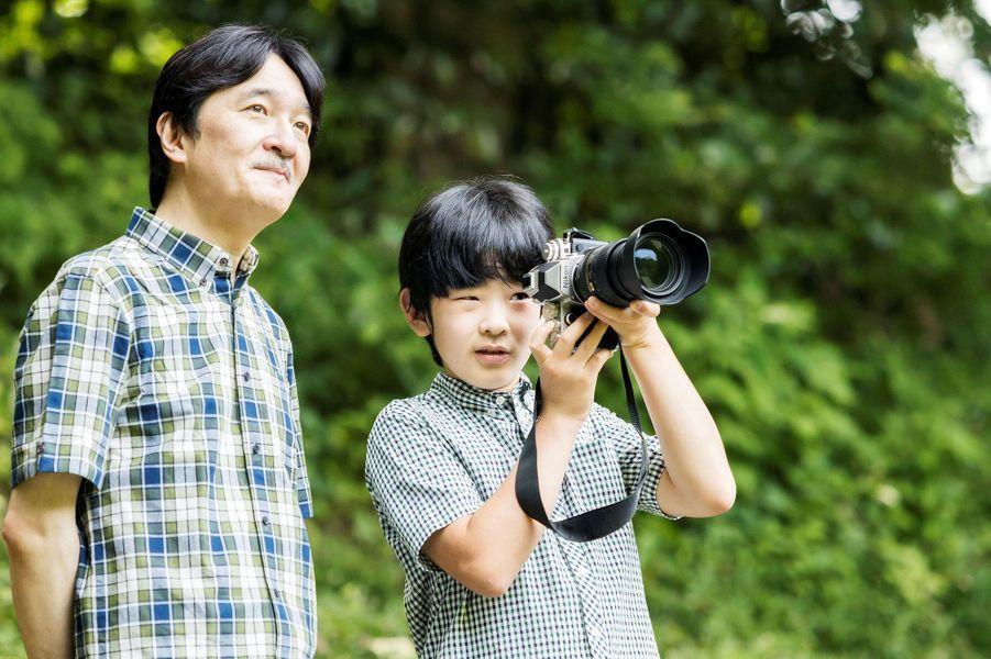 Le prince Hisahito du Japon avec son père, le prince héritier Fumihito d'Akishino, dans le jardin de leur résidence à Tokyo, le 10 août 2020. Photo diffusée le 6 septembre 2020 pour ses 14 ans