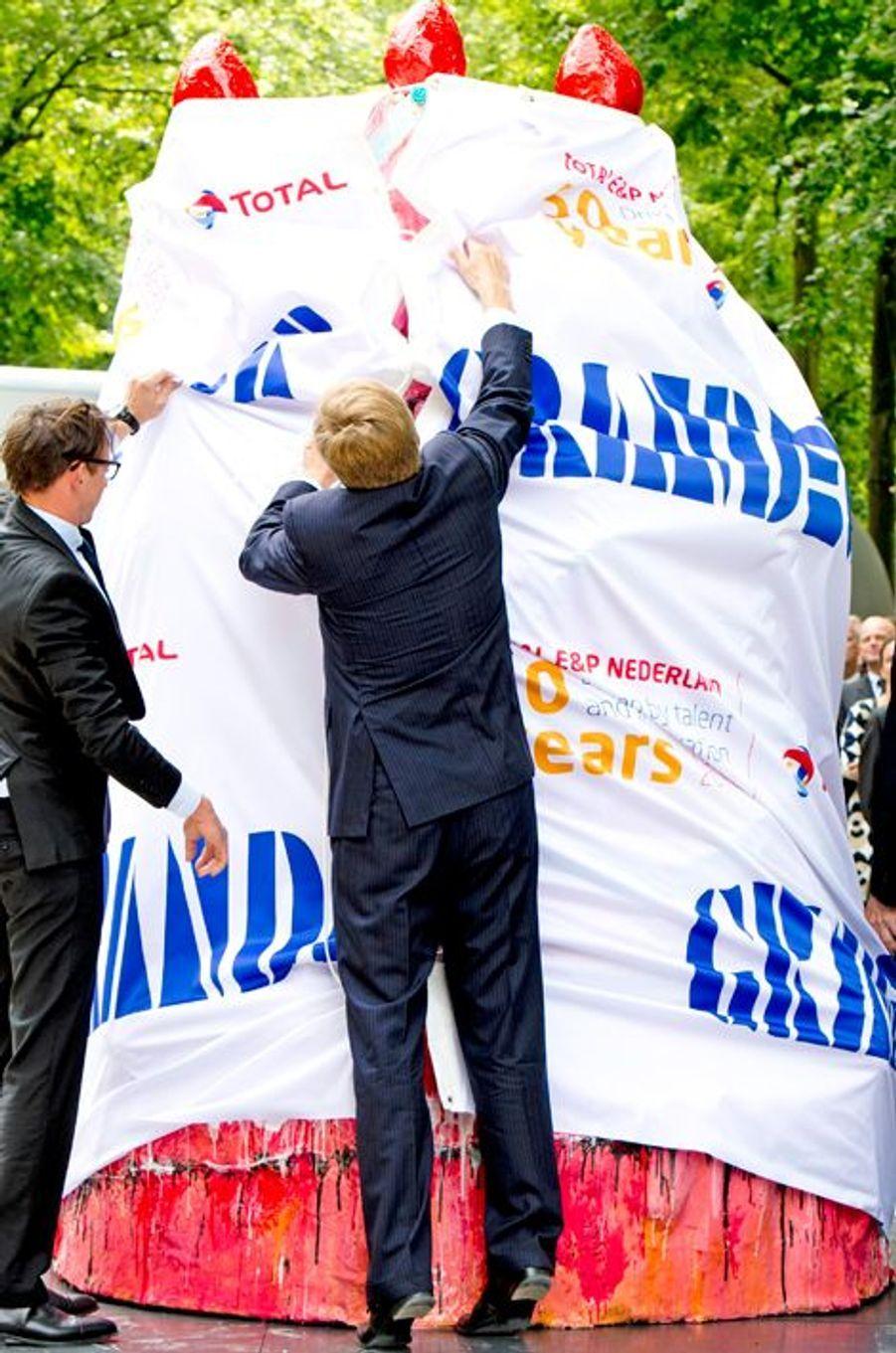 Willem-Alexander est bien curieux de voir ce qui se cache sous le papier, à La Haye le 17 juin 2014