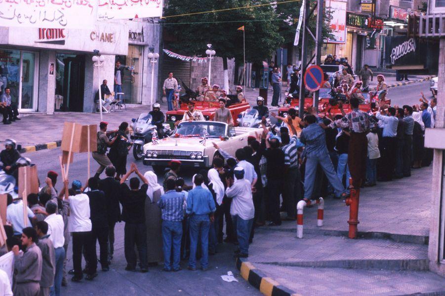 Le roi Abdallah II de Jordanie, avec la reine Rania, le jour de son intronisation le 9 juin 1999 dans les rues d'Amman
