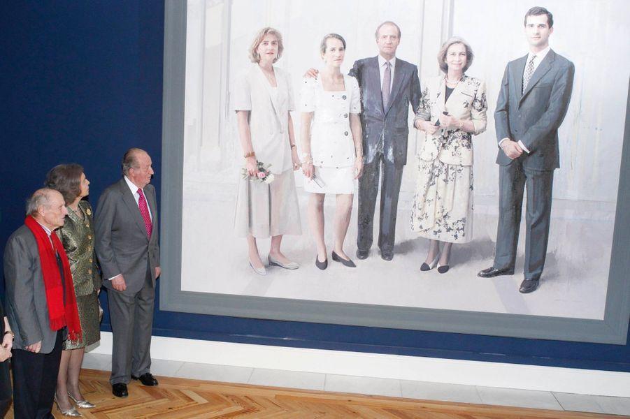 L'ex-roi Juan Carlors et son épouse Sophia devant le tableau d'Antonio López les figurant avec leurs trois enfants, à Madrid le 3 décembre 2...