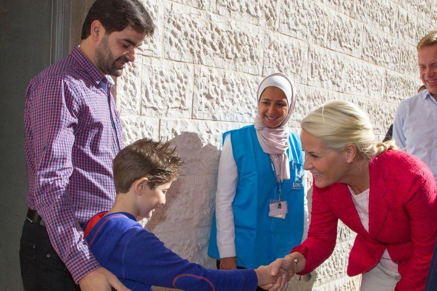 Mette-Marit et Haakon de Norvège accueilli par une famille syrienne résidant à Amman, le 22 octobre 2014