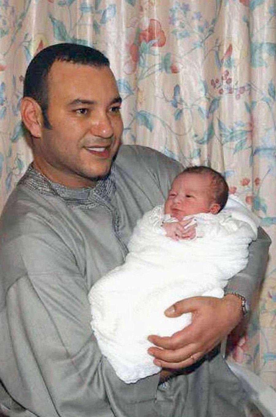Le prince Moulay El Hassan du Maroc, le 8 mai 2003, jour de sa naissance, dans les bras de son père le roi Mohammed VI