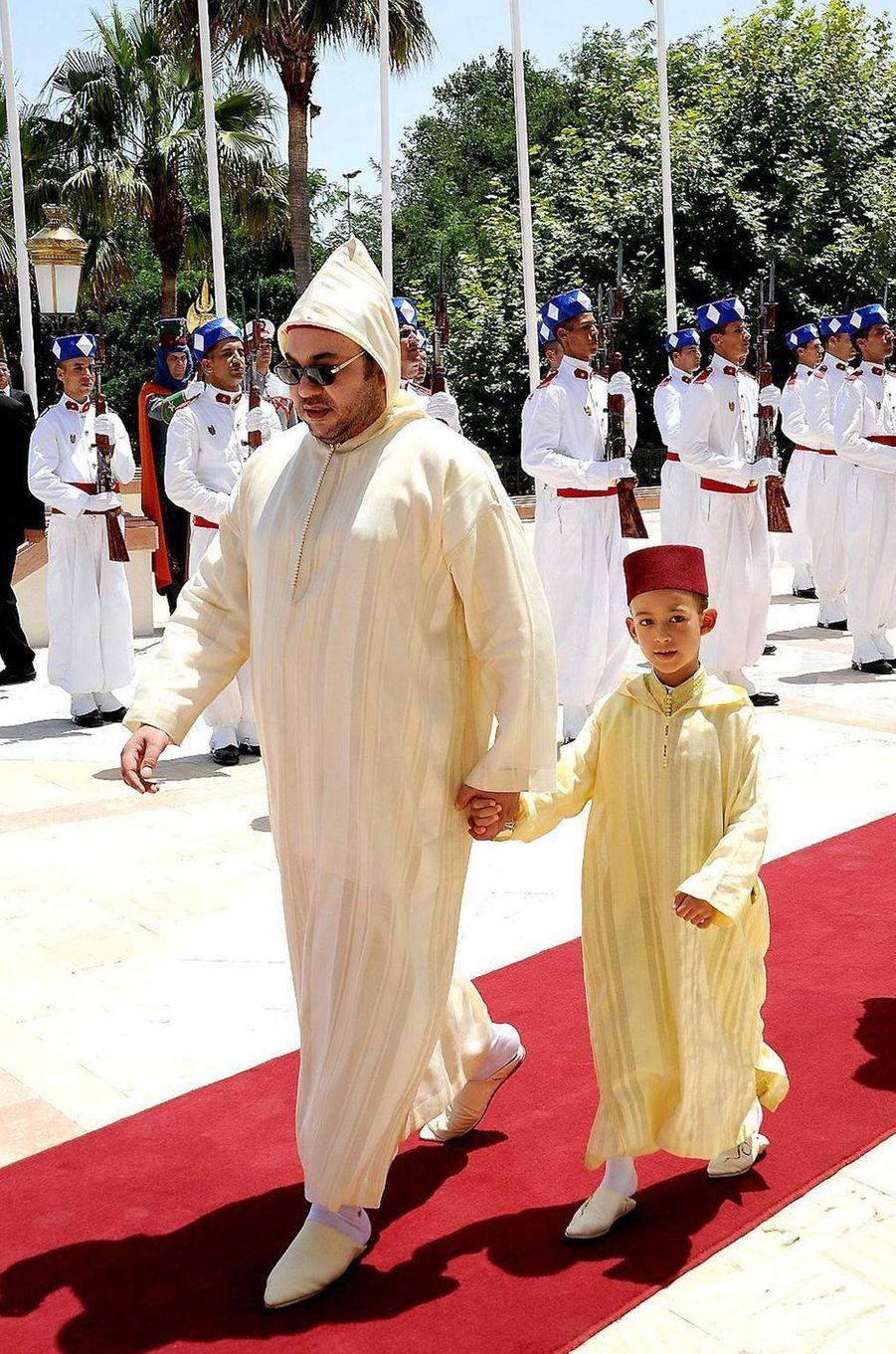 Le prince Moulay El Hassan du Maroc avec son père le roi Mohammed VI, le 30 juillet 2009