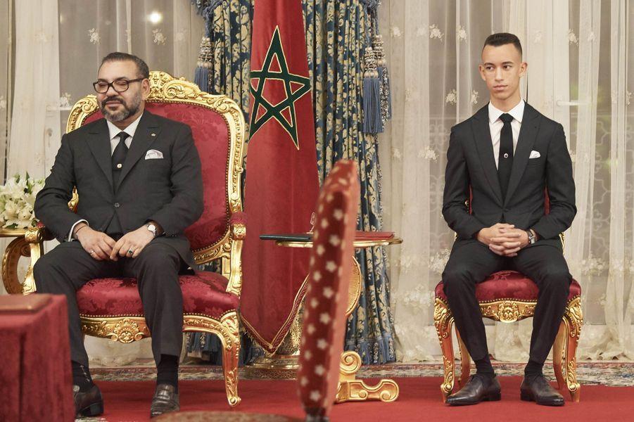 Le prince Moulay El Hassan du Maroc avec son père le roi Mohammed VI, à Rabat le 13 février 2019