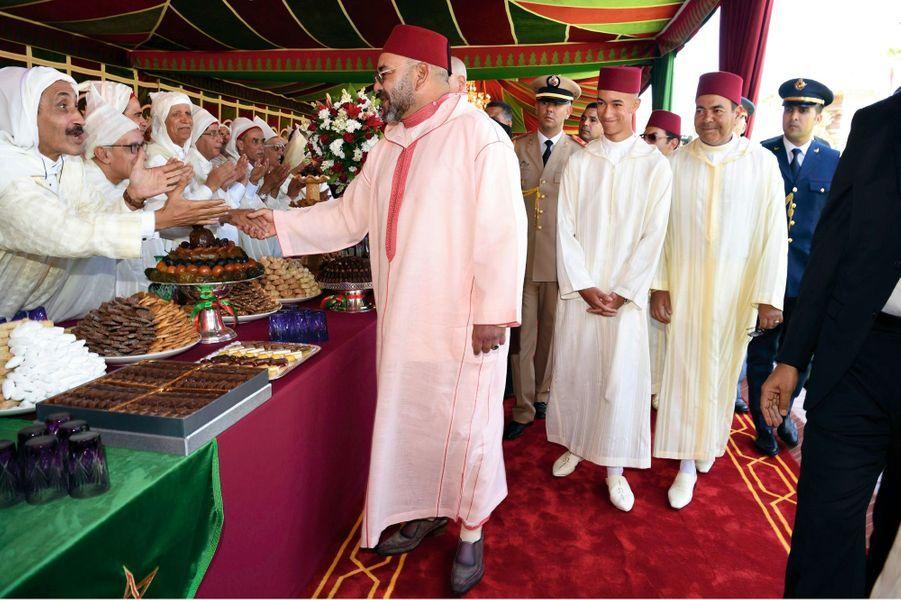 TOUJOURS SUIVI PAR SON FILS ET PAR SON FRÈRE, revêtus comme lui de la traditionnelle djellaba et coiffés d'un tarbouch rouge, le roi salue ses invités.